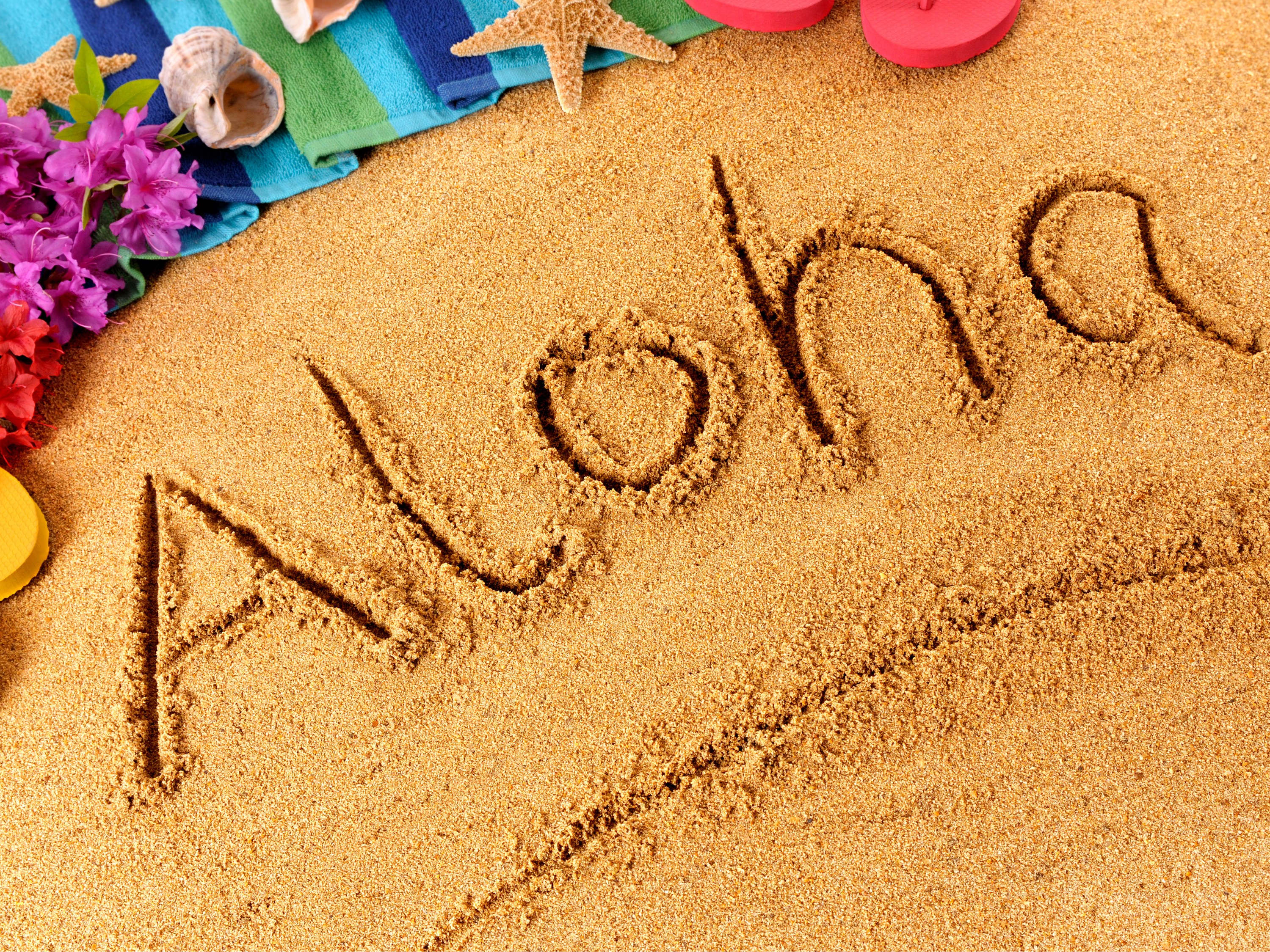 """illustration of beach with flowers toward the back with the word """"Aloha"""" drawn in the sand"""