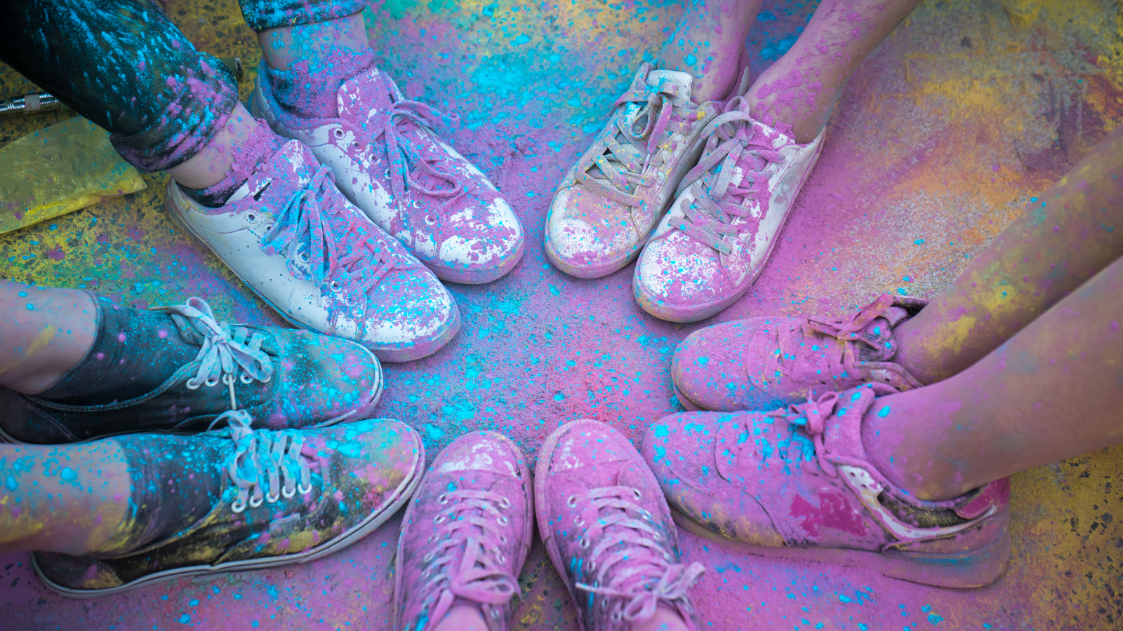 Children's shoes pushed together with pastel rainbow color powder on them