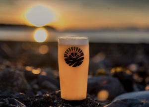 vitamin sea beer in a glass on the beach at sunset